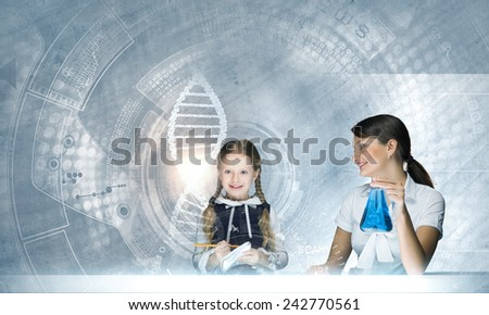 Young teacher and her pupil doing tests at chemistry lesson - stock photo