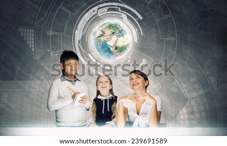 Young teacher and her pupils examining Earth planet. Elements of this image are furnished by NASA - stock photo