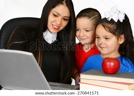 Young teacher and her pupils looking at laptop - stock photo