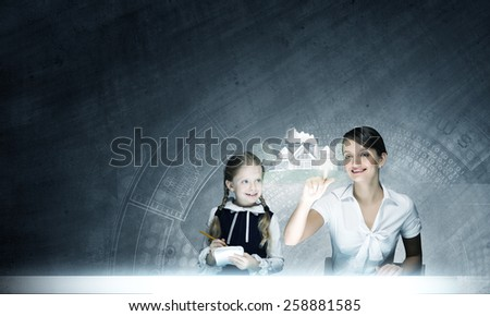 Young teacher and school girl at computing lesson - stock photo
