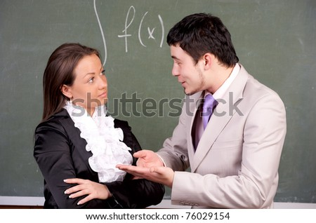 Young teacher and student discussing something in classroom - stock photo