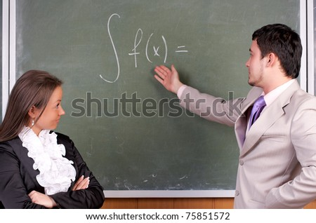 Young teacher and student doing exercise on blackboard
