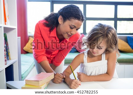 Young teacher assisting girl writing on notebook in school library - stock photo