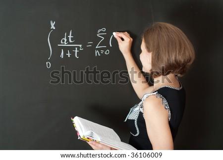 Young teacher is standing near blackboard in classroom - stock photo