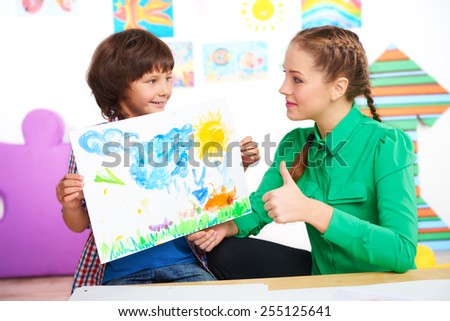 Young teacher looking at finished drawing of boy and showing thumb up. Lesson in preschool center for children - stock photo