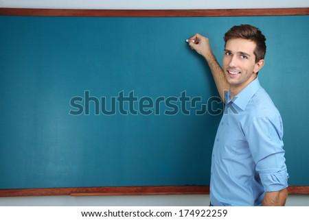 Young teacher near chalkboard in school classroom - stock photo