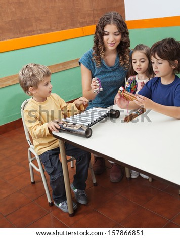 Young teacher playing musical instruments with children in classroom - stock photo