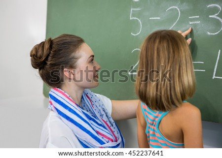 Young teacher teaching girl on chalkboard in classroom
