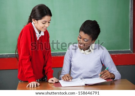 Young teacher teaching little schoolgirl at desk in classroom