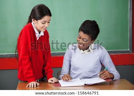 Young teacher teaching little schoolgirl at desk in classroom - stock photo