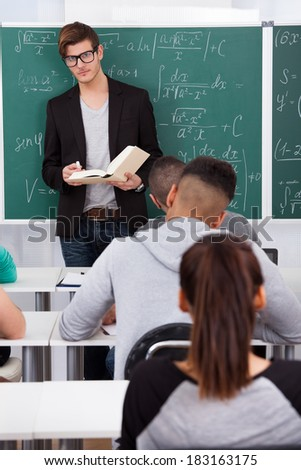 Young teacher teaching mathematics to university students in classroom - stock photo