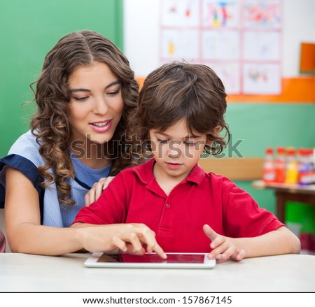 Young teacher teaching students to use digital tablet in classroom - stock photo
