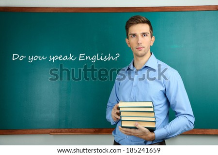 Young teacher with books near chalkboard in school classroom - stock photo