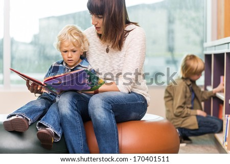 Young teacher with boy reading book in library - stock photo