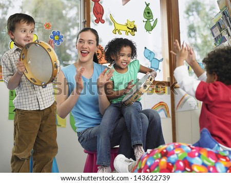 Young teacher with children playing music in classroom - stock photo