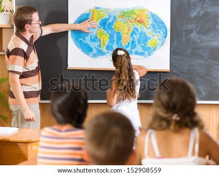 Young teacher with his class at geography lesson
