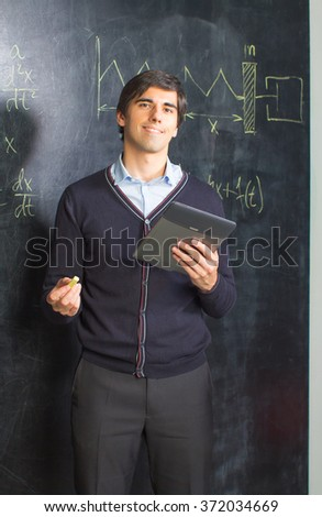 Young teacher with laptop and chalk - stock photo