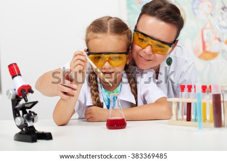 Young teacher with little student at elementary science class - conducting a chemistry experiment - stock photo