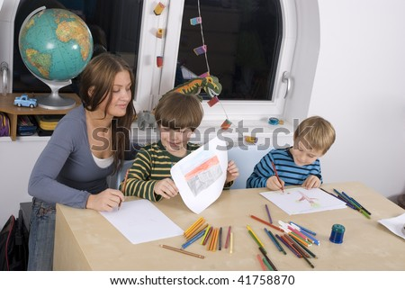 Young teacher with  students in a classroom. - stock photo