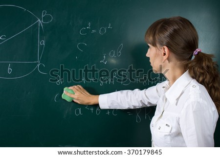Young teacher woman or student girl at the blackboard with math equation - stock photo