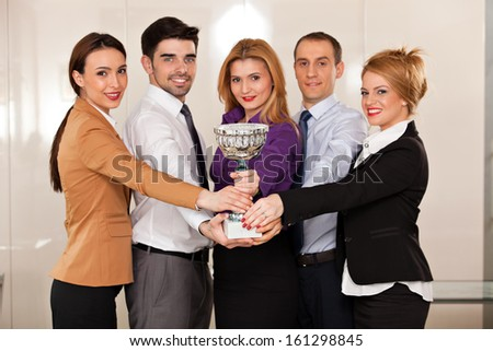 young team holding a trophy; happy business people celebrating their victory, focus on the trophy