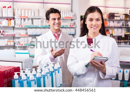 Young team of a pharmaceutist and technician working at chemist shop