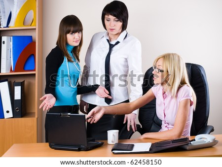 Young team of businesswomen with laptop in office - stock photo