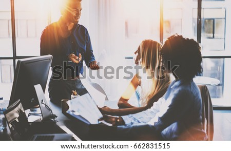 Young team of coworkers making great meeting discussion in modern sunny office.Teamwork concept.Hispanic businessman talking with two colleague woman.Horizontal,blurred background,flare effect
