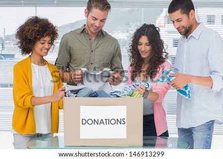 Young team of volunteers taking out clothes from a donation box for a charity - stock photo