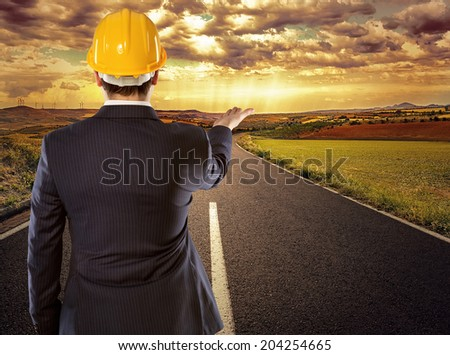 Young technician pointing at new architectural construction in perspective on the rural site.  - stock photo