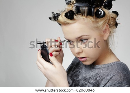 young teen age girl putting make up on to go out