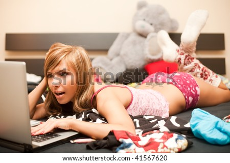 young teen blond woman in bed in chaos of clothes with laptop