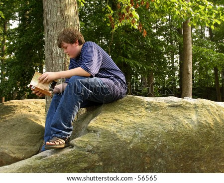 young teen boy reading a book outdoors - stock photo