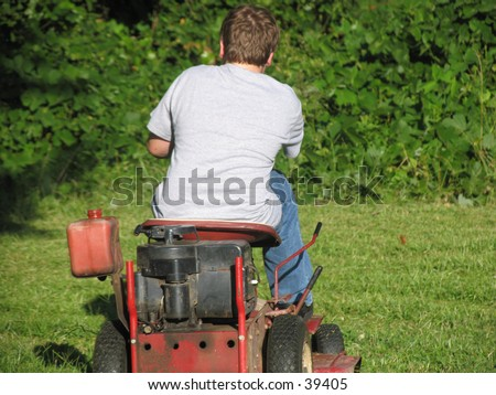 Young teen boy riding a lawn mower - stock photo
