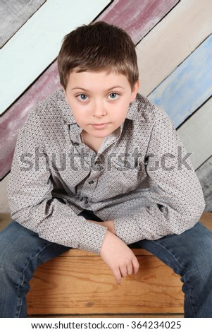 Young teen boy sitting on wooden crates - stock photo