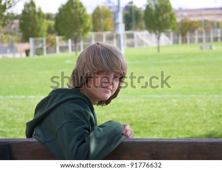 Young teen boy with long, shaggy hair, sitting on a bench in front of a park with green grass and trees. - stock photo