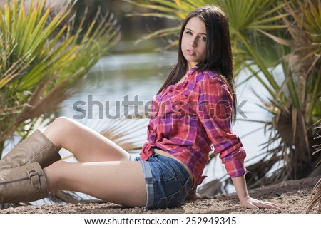 Young teen brunette laying down outdoors in red tied up flannel shirt - stock photo
