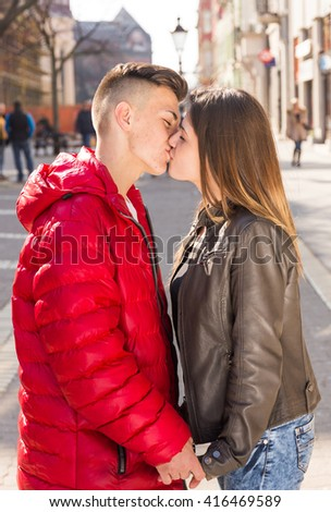 young teen couple kiss on walking street - stock photo