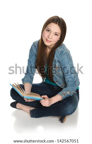 Young teen female student sitting on floor with a book, isolated on white, high angle view - stock photo