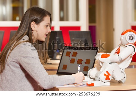Young teen girl playing with humanoid robot during school time - stock photo