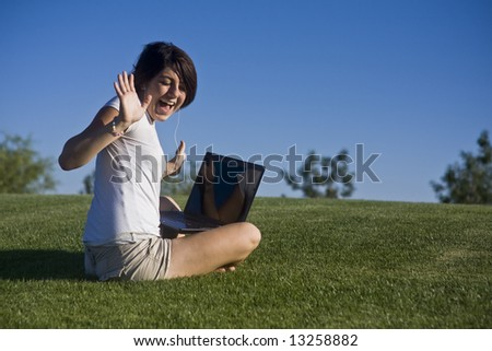 Young Teen Girl Sitting in Grass Listening to Music with Laptop