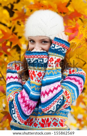 young teen girl wearing colorful sweater in autumn scenery