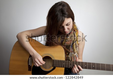 Young teen girl with nose ring playing acoustic guitar - stock photo