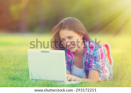 Young teen girl with white laptop computer lying down on green grass in the park