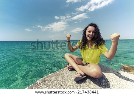 Young teen happy for successful holiday. Girl in yellow contrast shirt sitting at the edge and enjoying nice clean water and sky horizon. - stock photo