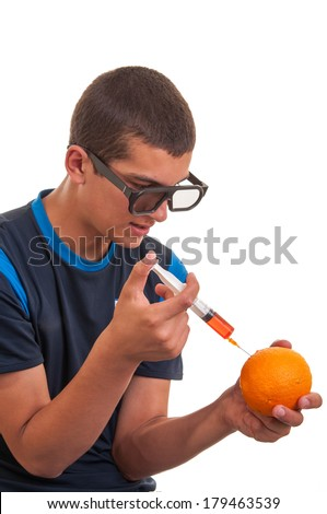 Young teen happy to do experiments with fruits for chemistry lab. Concept for genetically modified foods(GMO) - stock photo