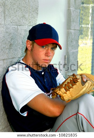 Young teen leans back against dugout wall.  He is holding his glove and has a serious look on his face. - stock photo