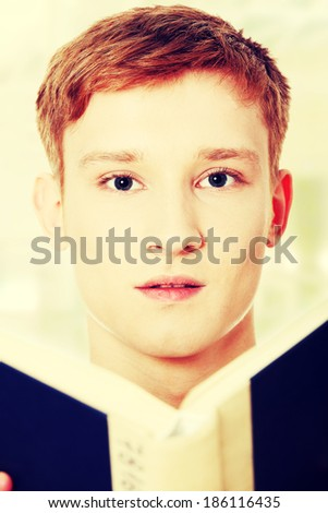 Young teen man is reading a book - stock photo