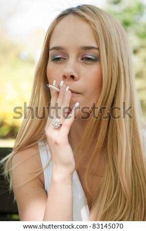 Young teen person smoking cigarette outdoors - stock photo