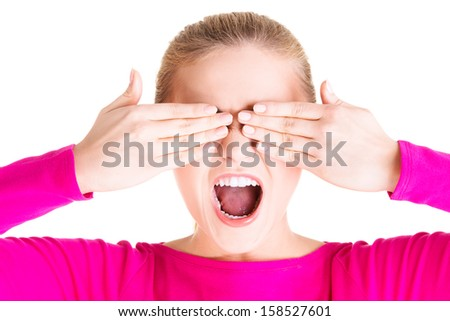 Young teen woman covering her face with hands, isolated on white - stock photo